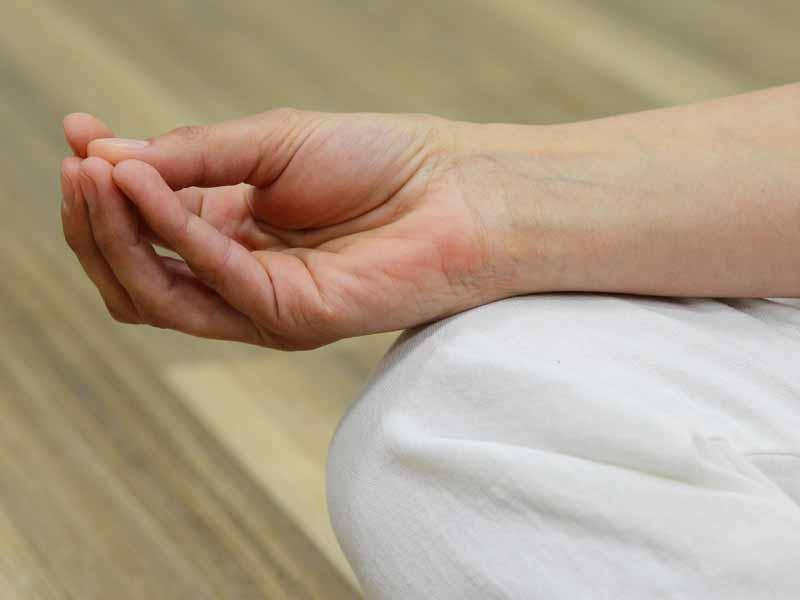 Das Beste - Meditation & Entspannung - Frau sitzt und hat die Hand in Meditationshaltung.